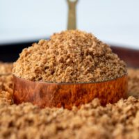 a measuring cup with gluten free breadcrumbs on a baking sheet