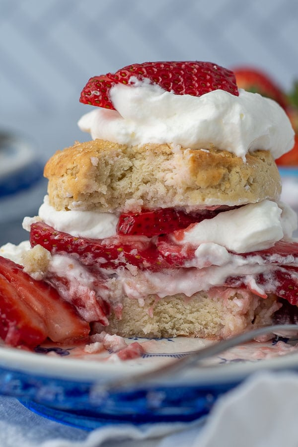 a bite taken out of strawberry shortcake on a white plate with a fork laying next to it