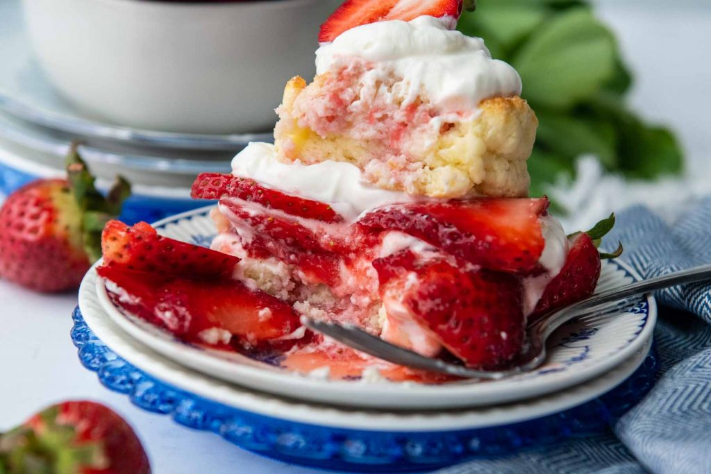 strawberry shortcake with a messy bite taken out on a blue plate