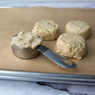 a biscuit in a measuring cup about to be placed on baking sheet