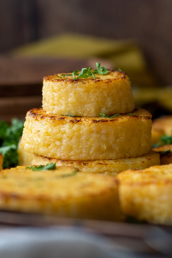 a stack of cheese grit cakes with fresh parsley sprinkled on
