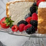 a gluten free angel food cake on a cake stand cut open with berries spilling out