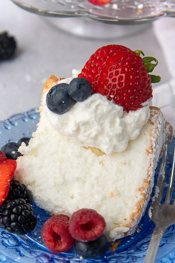 a slice of angel food cake with berries around it, whipped cream on top, and sliced strawberry
