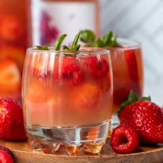 a close up straight on picture of rose sangria on a wooden plate with fresh berries laying next to it
