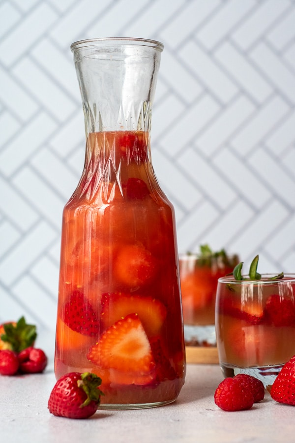 a pitcher of rose sangria with strawberries laying next to it and a glass of it in the background