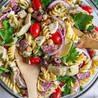 overhead shot of cold pasta salad with wooden spoons sticking out of bowl