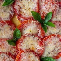 a pan of baked tomatoes with broiled cheese on top