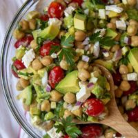 a wooden spoon holding up a serving of chickpea avocado salad