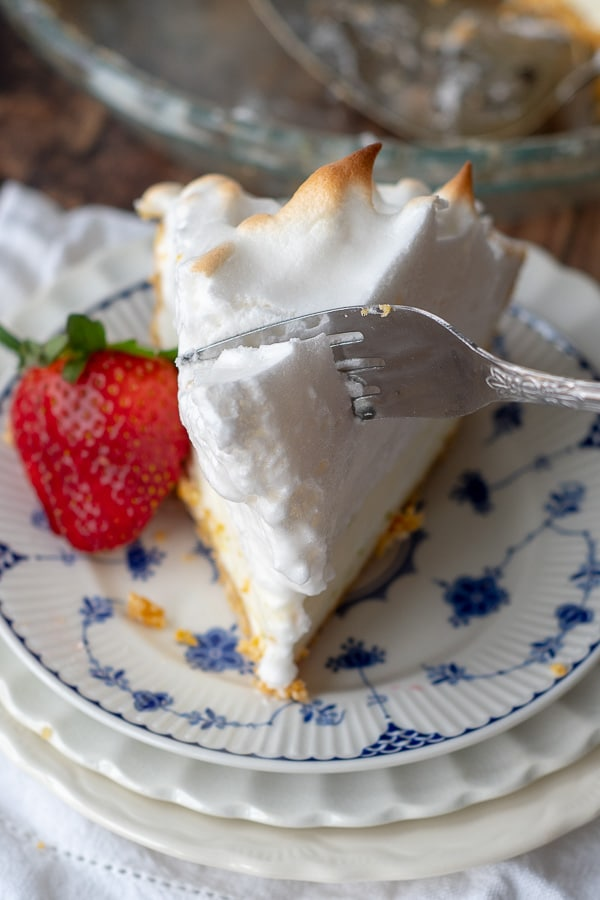 a fork slicing into the meringue on top of the frozen lemon pie