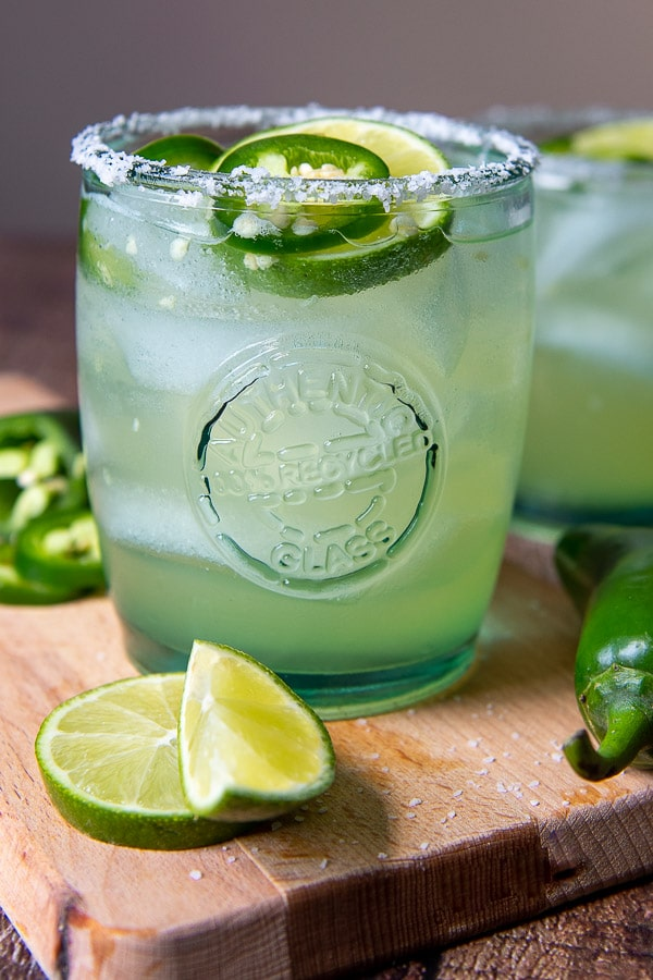 a margarita on a wooden cutting board with fresh jalapenoes and limes around it