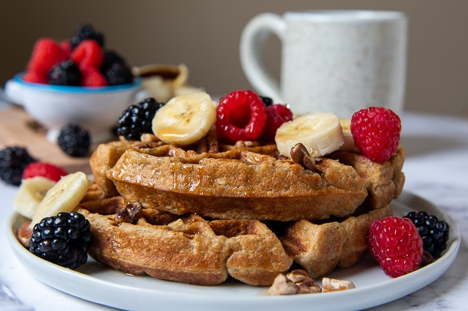 close up of a stack of 2 waffles with sliced bananas and berries on top