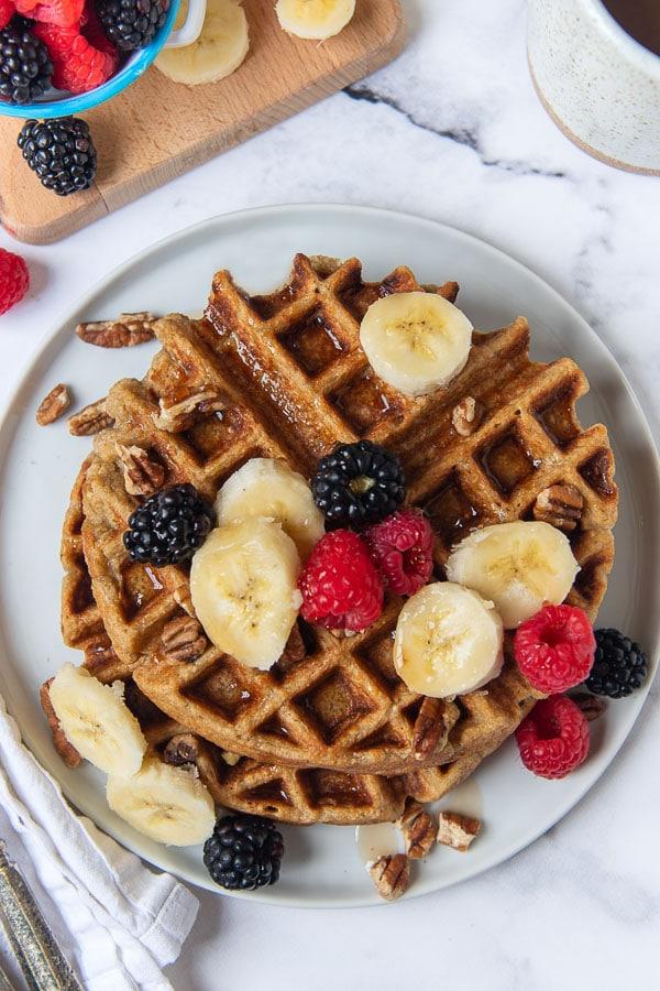 overhead shot of gluten free banana oatmeal waffles on a white plate