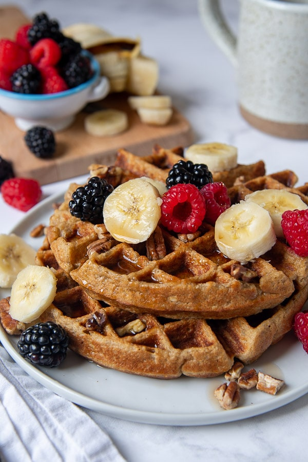 shot of gluten free waffles on a plate with berries, nuts, and bananas on top