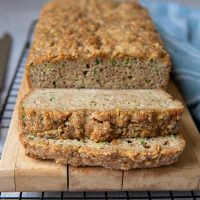 slices of zucchini bread falling down onto a wooden cutting board