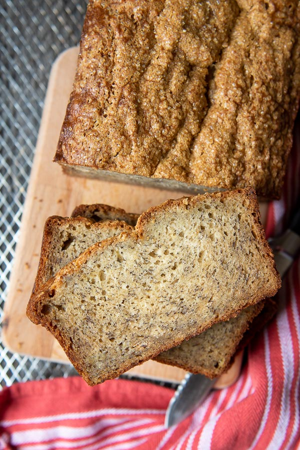 overhead shot of cut gluten free banana bread face up on a wooden cutting board