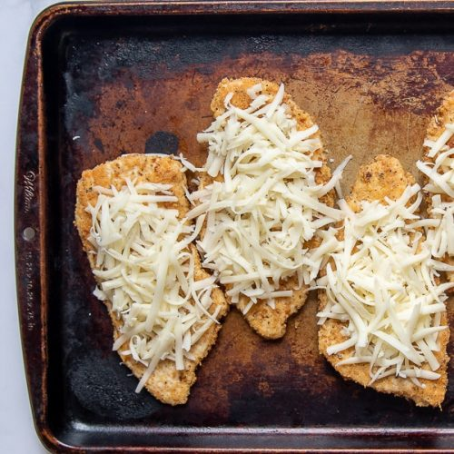 breaded chicken breasts on a baking sheet with grated cheese on top