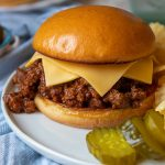 a close up of instant pot sloppy joes on a white plate with two slices of cheese