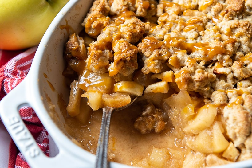 a spoon lifting out gluten free apple crisp with caramel drizzled over the topping