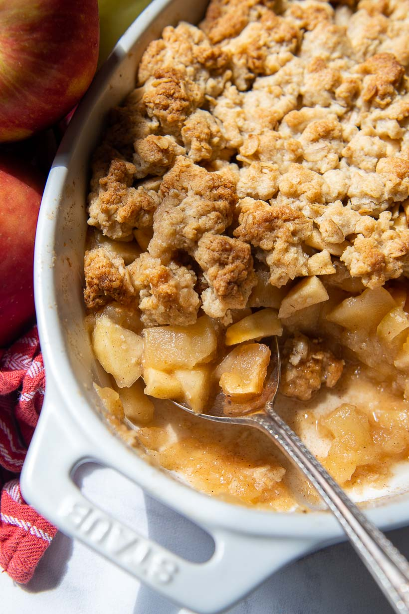 overhead shot of gluten free apple crisp in a white oval baking dish with a scoop taken out