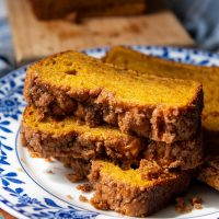 a stack of three slices of pumpkin bread with streusel topping on a blue and white flower plate