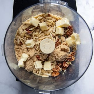 overhead of food processor with ingredients for nut crust
