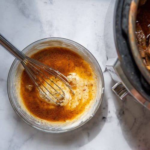 hot gravy from stroganoff being whisked into sour cream mixture