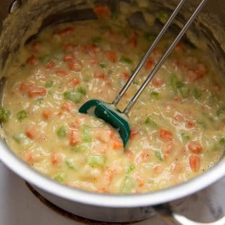 a spoon stirring the pot pie filling