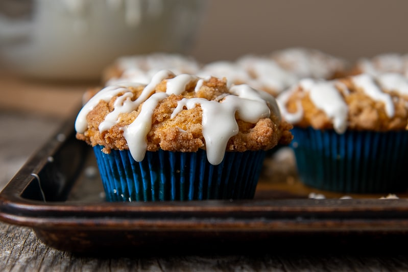 a straight on view of gluten free pumpkin muffin with crumb topping and glaze on top
