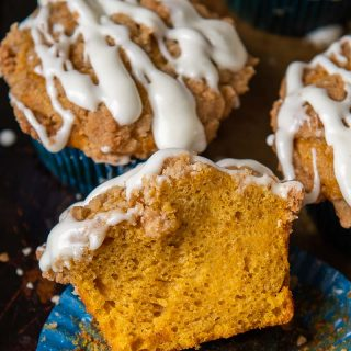 a pumpkin muffin split open and resting on a muffin liner
