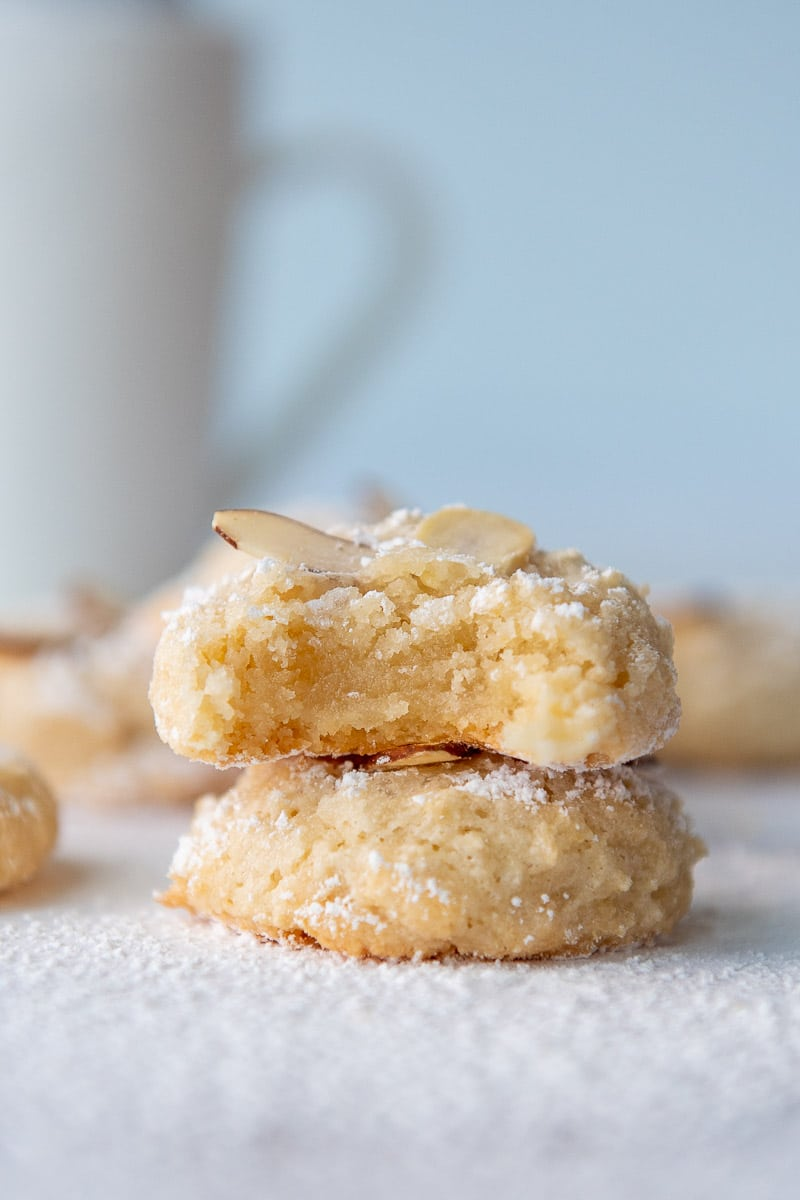 a stack of two almond paste cookies with the top one having a bite taken out