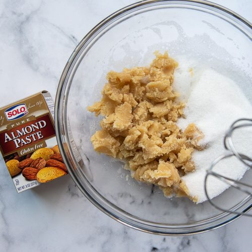 almond paste broken up in a bowl with sugar