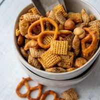 a small bowl of snack mix with a small scoop inside