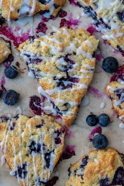 an overhead shot of a gluten free scone with blueberries and glazed drizzled on