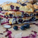 a stack of scones with fresh blueberries scattered around and spoon with frosting