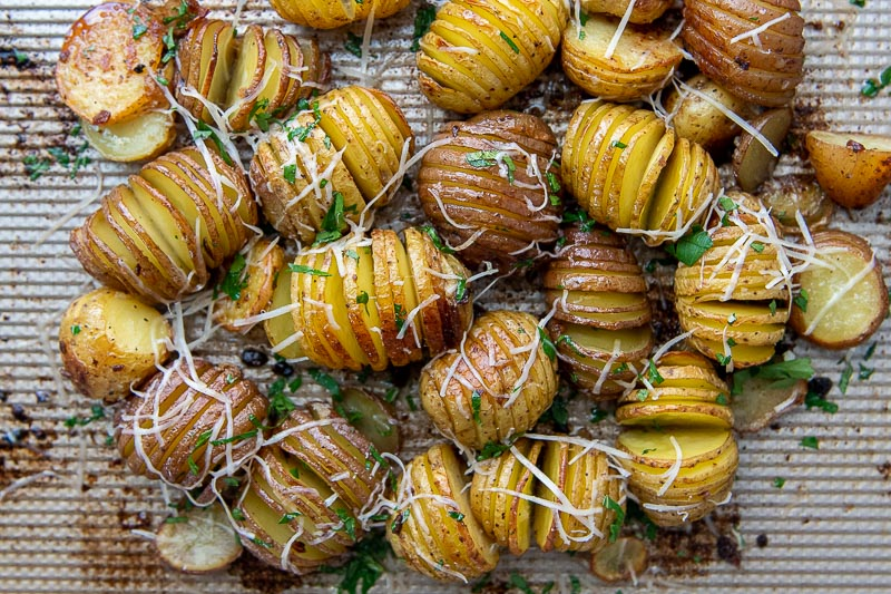 mini hasselback potatoes on a baking sheet with parmesan on top