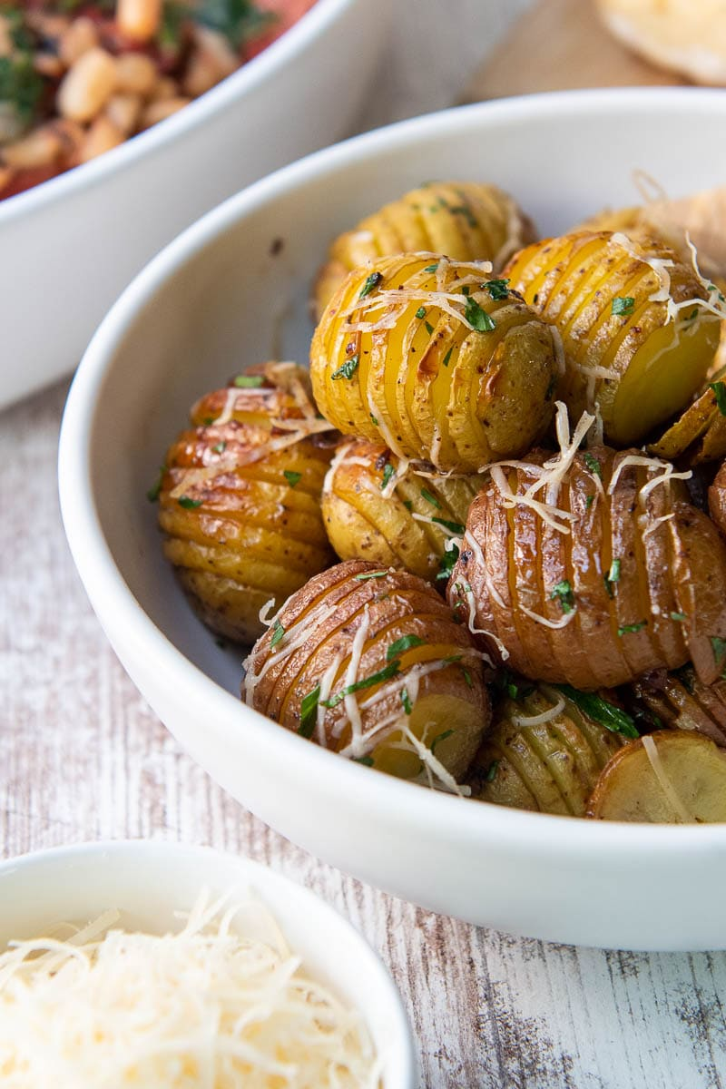 red potatoes in a while bowl with parmesan cheese and parsley