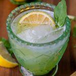a gin basil smash cocktail in a green glass with a lemon wedge and basil garnish