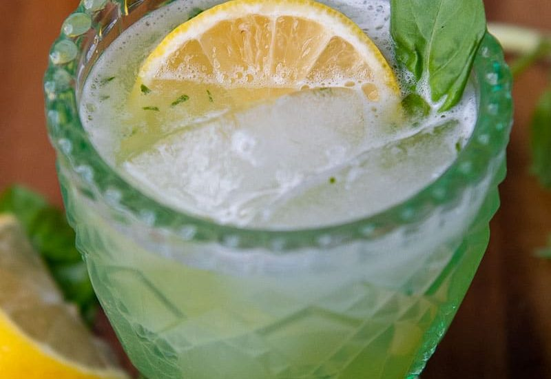a gin basil smash cocktail in a green glass with a lemon wedge and basil garnish