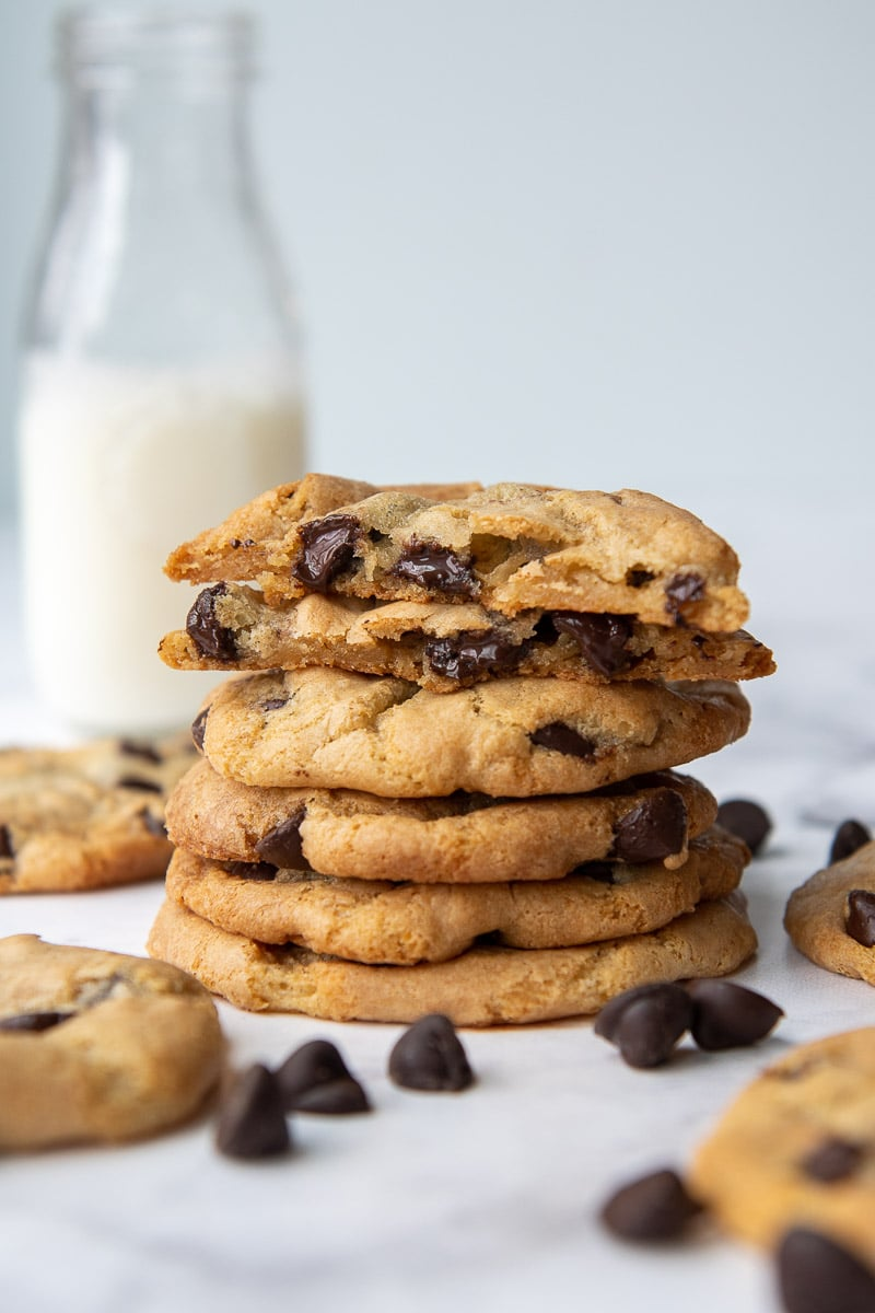 stack of chocolate chip cookies with glass of milk behind it