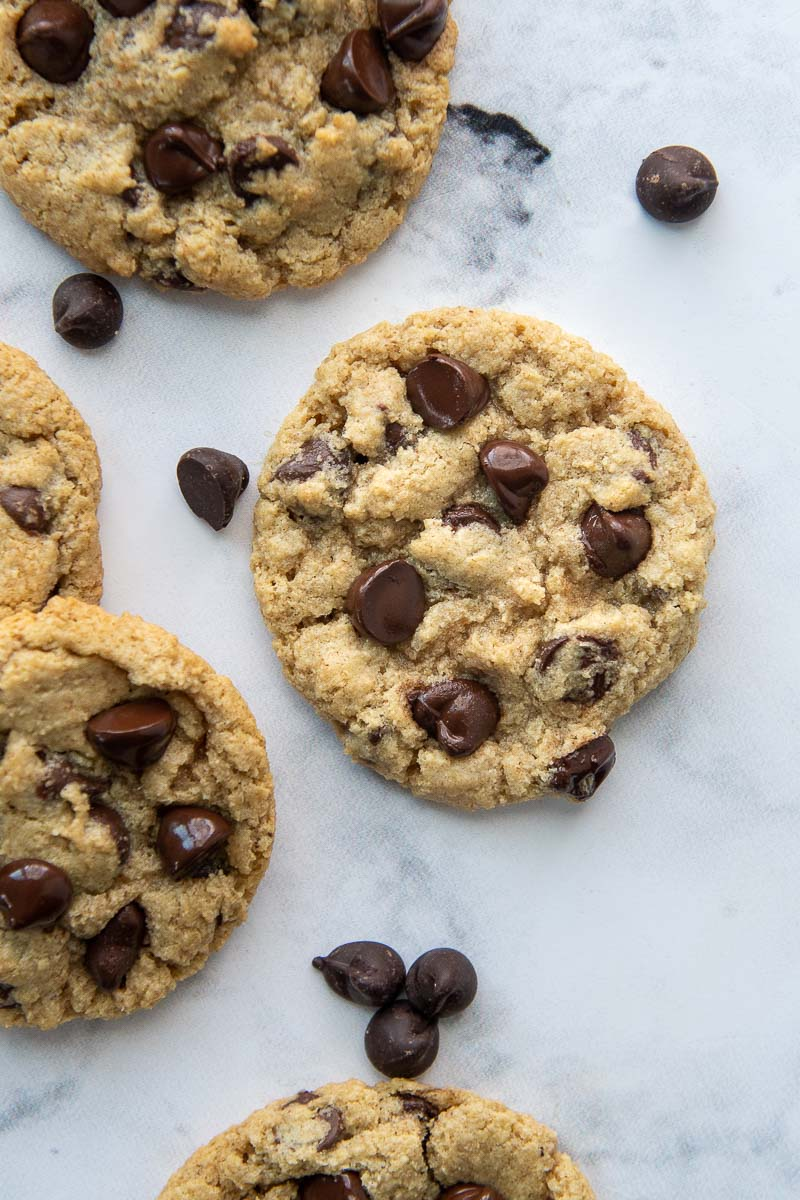overhead shot of chocolate chip cookies laying flat with chocolate chips scattered around