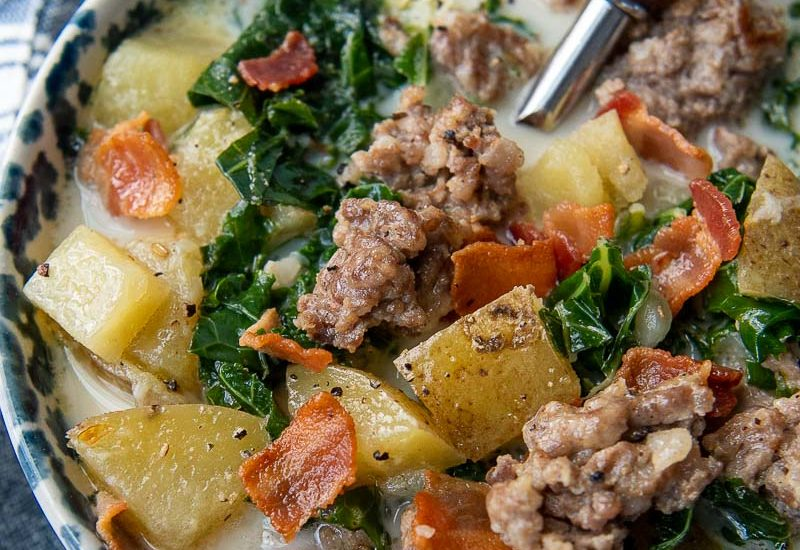 close up of zuppa toscana soup in a blue bowl with spoon going in