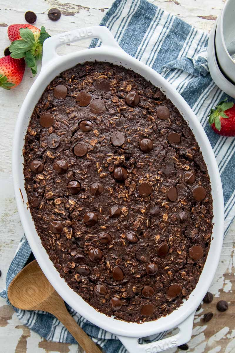 overhead shot of chocolate oatmeal in white oval baking dish with fresh strawberries laying next to it