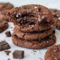 a stack of cookies with the top two having bites taking out and chocolate chunks laying around it