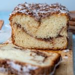 cinnamon swirl quick bread sliced open on a wooden cutting board