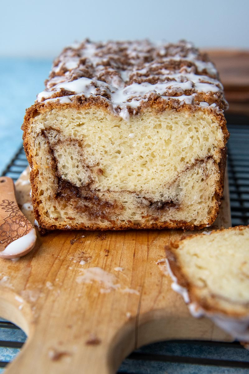 a slice of cinnamon bread on a cutting board with frosting over top
