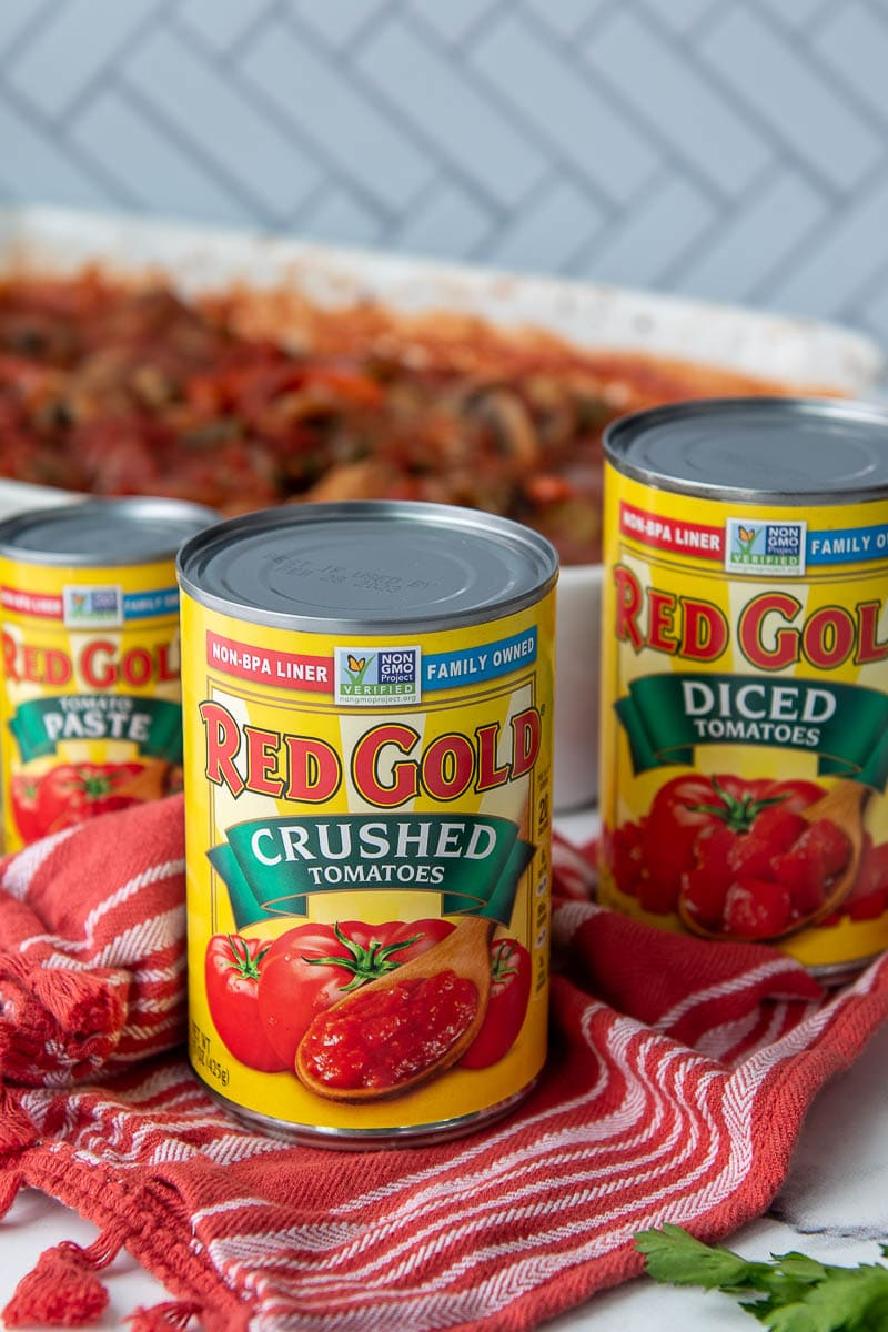 red gold tomato cans in front of chicken cacciatore