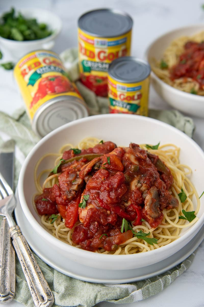 bowl of chicken cacciatore over pasta with red gold tomato cans in the background