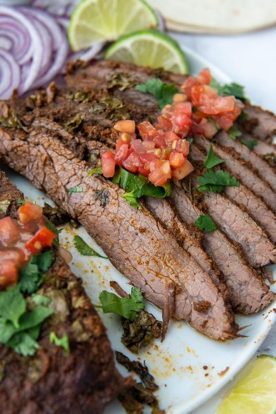 sliced flank steak on a plate with pico over top