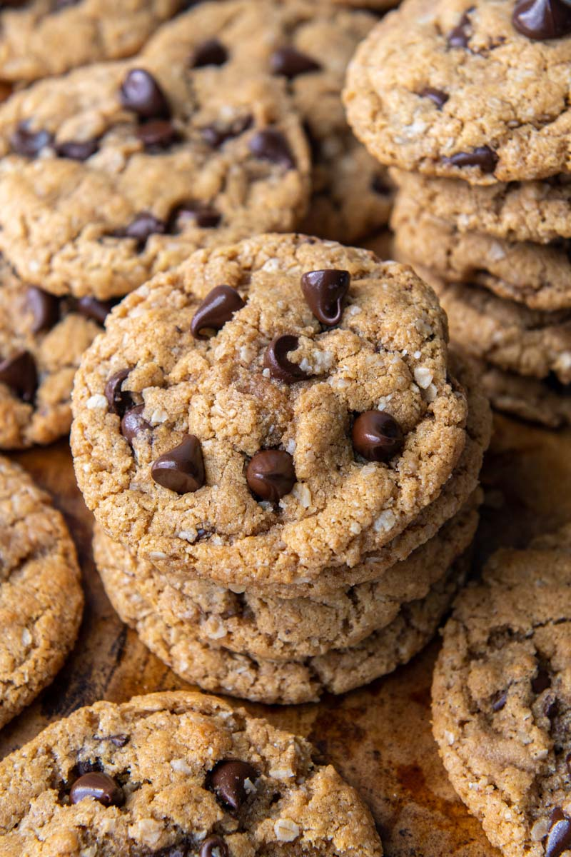 a stack of flourless peanut butter chocolate chip cookies with more laying around