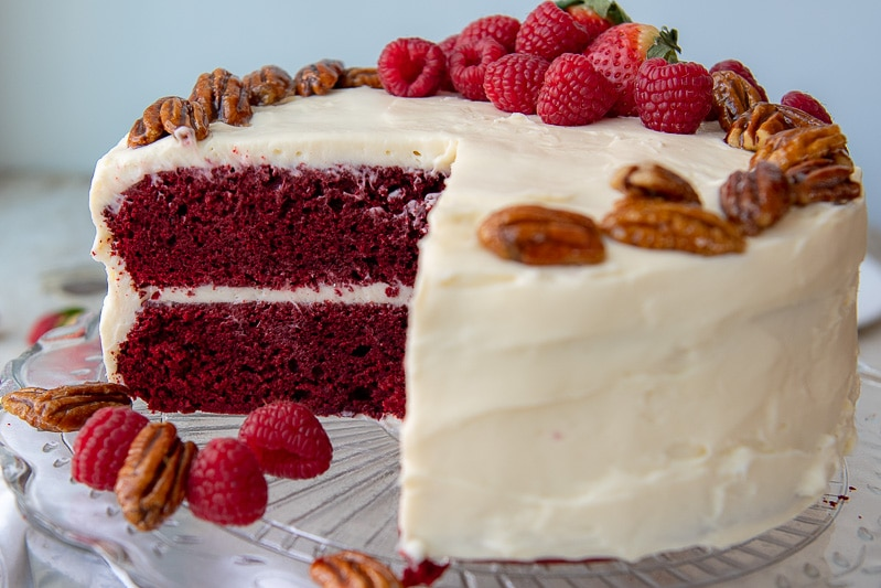 a cut red velvet cake on a glass platter with fresh berries around